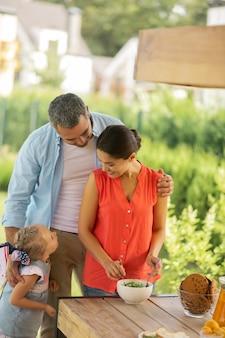 サラダを調理する妻。夏のテラスで夫と娘の近くに立ってサラダを調理する妻