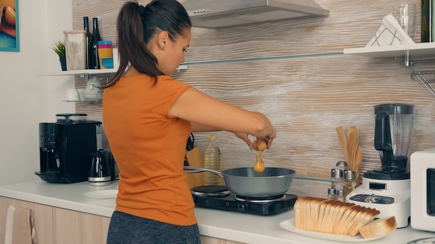 朝食のためにフライパンに卵を割る妻。新鮮な製品で健康的な朝、暖かい晴れた夏の朝の光の下で居心地の良いモダンなキッチンで料理をしている主婦のための幸せなライフスタイル