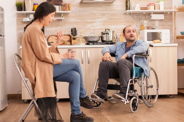 Wife crying because of disagreement with disabled husband in wheelchair. couple argue in kitchen. disabled paralyzed handicapped man with walking disability integrating after an accident.