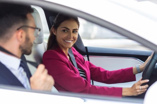운전하는 아내. 남편이 그녀의 근처에 앉아있는 동안 차를 운전하는 밝은 분홍색 재킷을 입은 검은 눈의 아내