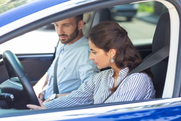 Жена за рулем. темноволосая красивая жена в полосатой блузке за рулем машины, пока машина сидит рядом с ней
