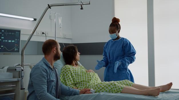 夫と一緒に病棟に座っている子供を期待している妻