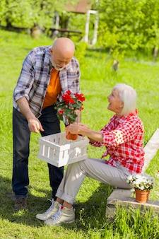 행복한 아내. 남편과 함께 꽃을 돌보는 행복을 느끼는 빛나는 회색 머리 아내