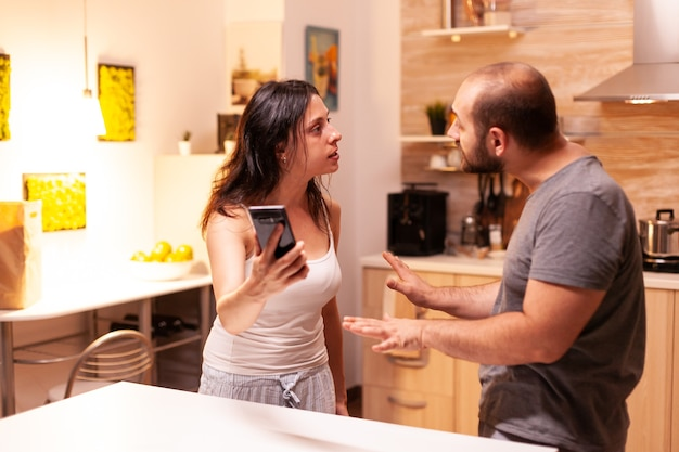 Wife fighting with cheating husband holding phone with texts from another woman. heated angry frustrated offended irritated accusing her man of infidelity showing him messages.