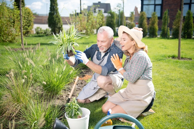 Wife in hat. excited wife wearing beige hat spending her morning near flower bed with her handsome mature husband
