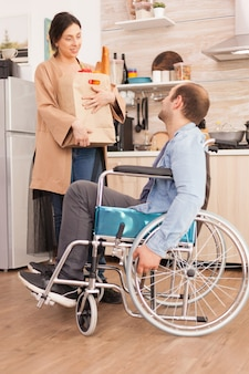 Wife holding paper bag with organic products in kitchen talking with disabled husband in wheelchair. disabled paralyzed handicapped man with walking disability integrating after an accident.