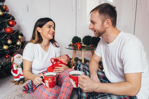 The wife and husband keeping cups of coffee and sitting on the floor