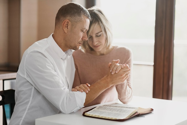 Wife and husband praying together at home