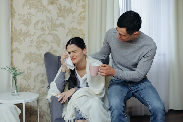 The wife is crying. husband brings a cup of tea and calms the woman
