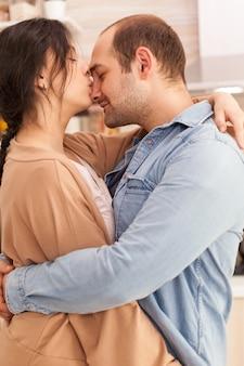 부엌에서 춤을 추면서 남편의 코에 키스하는 아내. 행복한 젊은 가족. 아내와 남편의 사랑, 로맨스, 부드러운 순간, 집에서의 재미와 행복, 공생 음악 쾌활하고 미소