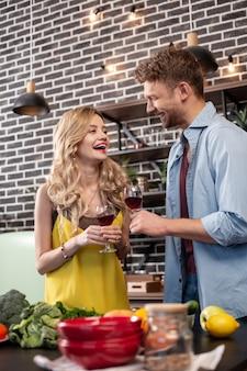 웃는 아내. 행복 한 금발 머리 아내는 그녀의 재미있는 남자와 저녁 식사를하는 동안 행복하고 웃고 느낌