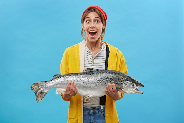 Жена рыбака держит в руках огромную рыбу с удивленным выражением лица, с вытаращенными глазами и отвисшей челюстью, не веря своим глазам, радуясь удачному улову. счастливый шокирован рыбак с форелью