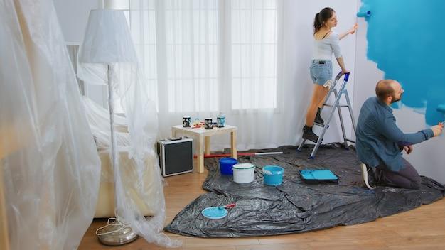 Жена на лестнице красит стену квартиры с помощью роликовой щетки. ремонт квартир и строительство дома одновременно с ремонтом и благоустройством. ремонт и отделка.