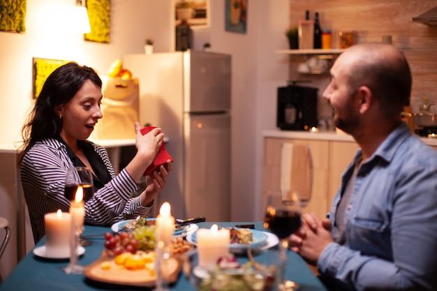 ロマンチックなディナーの間に夫によって提示された小さなギフトボックスを開く妻。結婚記念日を祝う食事を楽しんで、家で一緒に食事をする幸せな陽気なカップル