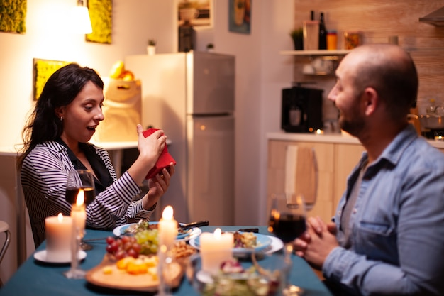 Wife opening small gift box presented by husband during romantic dinner. happy cheerful couple dining together at home, enjoying the meal celebrating their anniversary