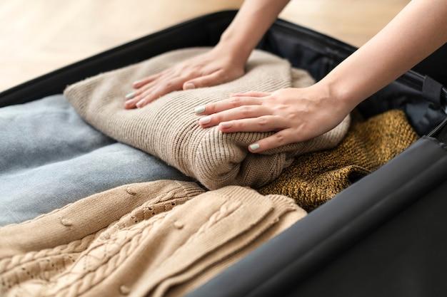 Moglie che prepara i suoi vestiti invernali in una valigia per un viaggio