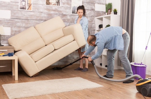 Wife picks up sofa while her husband is cleaning the dust under it with vacuum cleaner