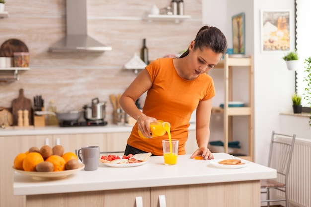 Жена наливает свежий сок в стакан на завтрак на кухне