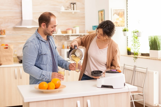 남편이 잔을 들고 있는 동안 아내가 맛있는 스무디를 붓고 있습니다. 건강하고 평온하고 쾌활한 생활 방식, 다이어트를 먹고 포근하고 화창한 아침에 아침 식사를 준비합니다.