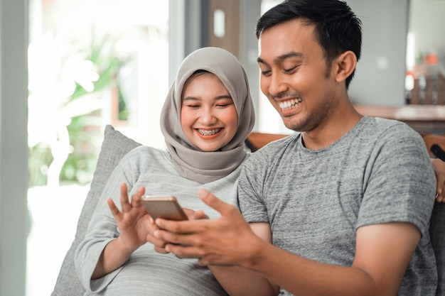 妊娠中の妻と夫がスマートフォンを使用して