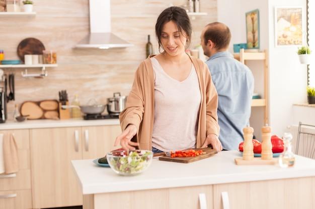 Вайф тянется за салатником на кухне, за ней стоит муж. счастливая в любви веселая и беззаботная пара, помогая друг другу готовить еду