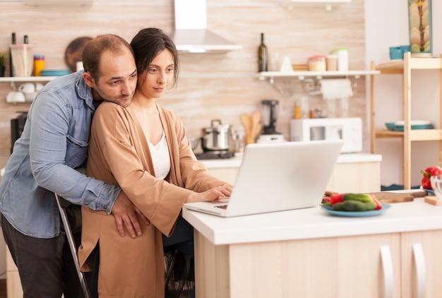 남편이 그녀를 껴안고 있는 동안 아내가 부엌에서 노트북을 읽고 있습니다. 현대적인 wi-fi 무선 인터넷 기술을 사용하여 집에서 사랑하는 부부의 행복한 사랑의 쾌활한 낭만적인