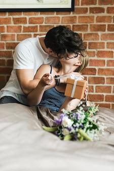 Жена получает подарочную коробку и букет цветов от мужа