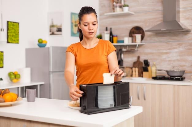 아침 식사를 위해 전기 토스터기에 빵 조각을 굽는 아내.
