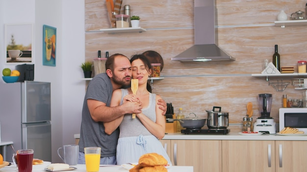 パジャマを着てキッチンで夫と踊りながら木のスプーンで歌う妻。のんきなカップルが笑って楽しんで面白い人生を楽しんでいる本物の既婚者ポジティブ幸せな関係