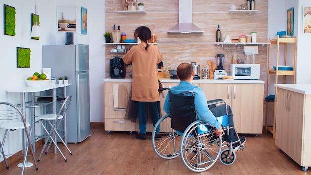 시장에서 도착한 후 부엌에서 휠체어를 타고 마비된 남편의 식료품 가방을 가져간 아내. 휠체어를 돕고 회복하는 마비된 장애 장애 핸디캡 장애 남자.