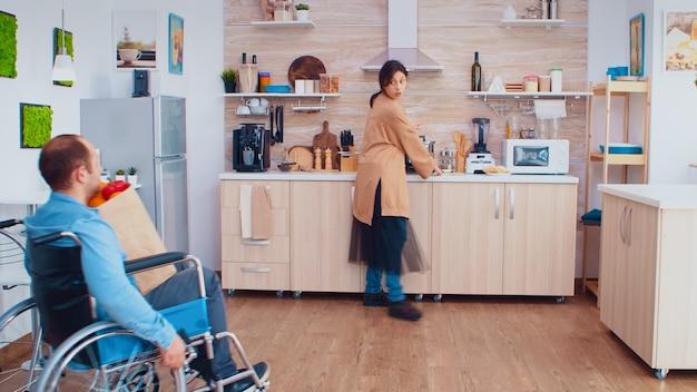 부엌에 있는 슈퍼마켓에서 도착한 후 휠체어를 타고 장애인 남편에게서 식료품 가방을 가져가는 아내. 휠체어를 돕고 회복하는 마비된 장애 장애 핸디캡 장애 남자.