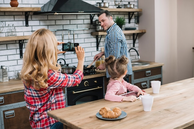 Wife taking photograph of her husband in mobile phone while cooking in kitchen