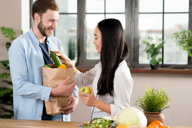 Wife taking vegetable from husband holding brown grocery bag in kitchen