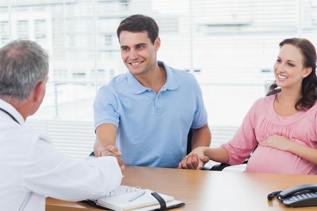 彼の期待するwifesの手を保持しながら彼の医者と手を振る笑顔の男