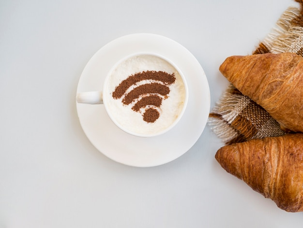 Wifi symbol in cup with croissants