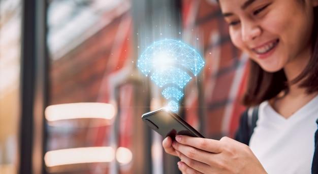 Технология беспроводной связи и сети, улыбающиеся азиатские женщины с помощью смартфона показывают значок wifi в торговом центре.