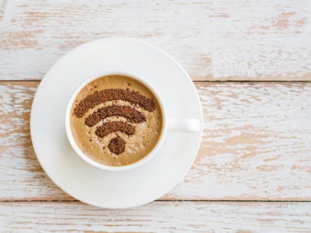 木製の背景の上にカップに描かれたwifiシンボル