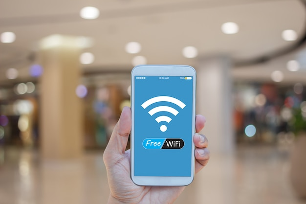 ショッピングモールの背景にぼやけて画面上に無料のwifiとスマートフォンを持っている手