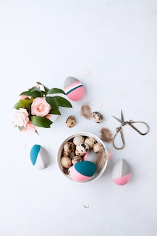自然に染めたウズラの卵と色のイースターエッグのフラットレイアウト構成は、羽とピンクのバラのwihteテーブルウォールのトレイに横になっています。テキストのためのスペース