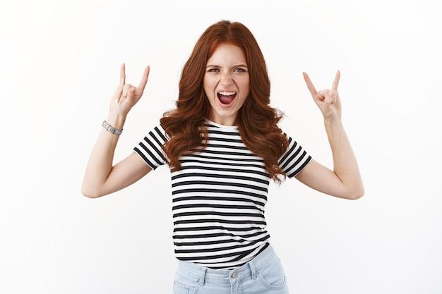 줄무늬 티셔츠를 입은 거칠고 근심 없는 잘 생긴 빨간 머리 소녀는 흥분하고 로큰롤, 헤비메탈 제스처, 입을 벌리고 열광적이고 낙관적이며 멋진 파티를 즐깁니다.