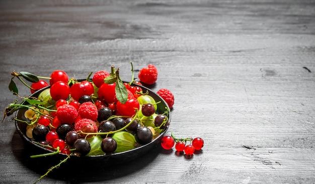 Дикие ягоды в старой тарелке на черном деревянном столе.