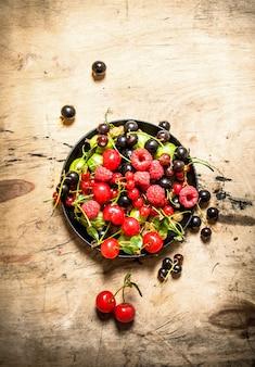 Лесные ягоды в старой тарелке. на деревянном столе.
