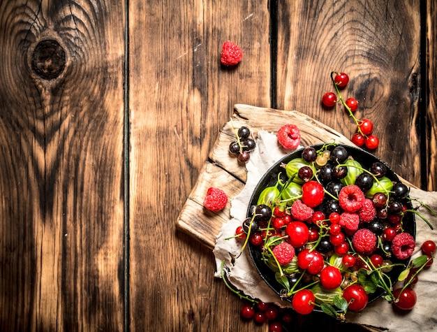 Лесные ягоды в старой тарелке на доске. на деревянном фоне.