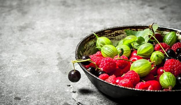 Лесные ягоды в старой тарелке. на каменном столе.