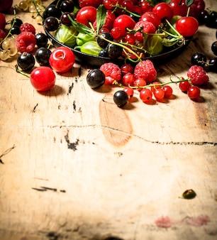 나무 테이블에 오래 된 접시에 야생 딸기