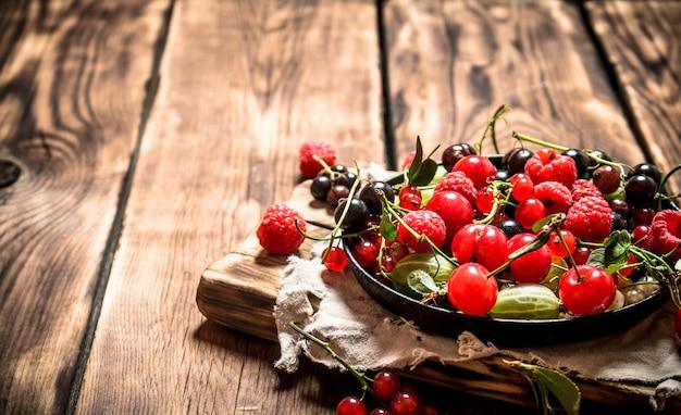 Лесные ягоды в старой тарелке на деревянном столе.