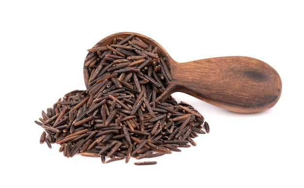 Wild black rice in wooden spoon, isolated on white background.
