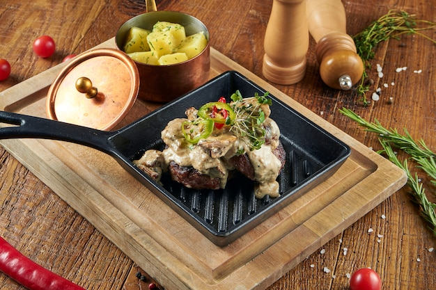 Wild boar cutlets with boiled potatoes and creamy sauce with wild mushrooms on a wooden surface in composition with spices on a wooden surface