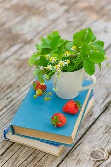 古い素朴な木製のテーブルの本の白いカップに野生のヒナギクとイチゴ