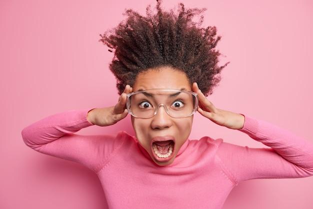 야생의 감정적 겁에 질린 여성이 충격을받은 머리를 움켜 쥐고 입을 크게 벌리고 공포에 부끄러운 비명을 지르며 투명한 안경과 터틀넥을 착용합니다.